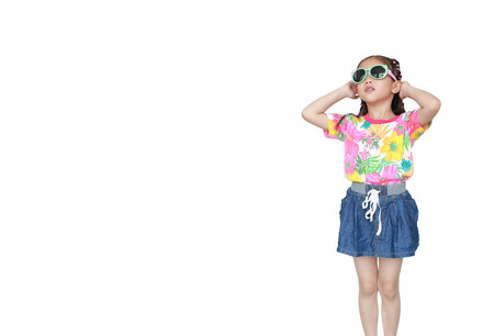 Jolie petite fille asiatique portant une robe d'été à fleurs et des lunettes de soleil isolées sur fond blanc. Prêt pour les vacances d'été. Banque d'images