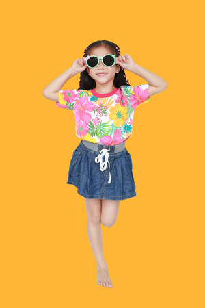 Cute little Asian kid girl wearing a flowers summer dress and sunglasses isolated on yellow background. Summer and fashion concept.