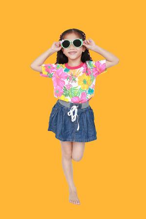 Niña linda niño asiático con un vestido de verano de flores y gafas de sol aisladas sobre fondo amarillo. Concepto de verano y moda.