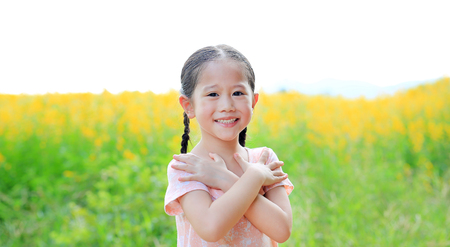 Adorable little Asian child girl feeling free with hand folded (cross one's arm) in Sunhemp field with sunlight outdoor. Yellow flowers background. Reklamní fotografie