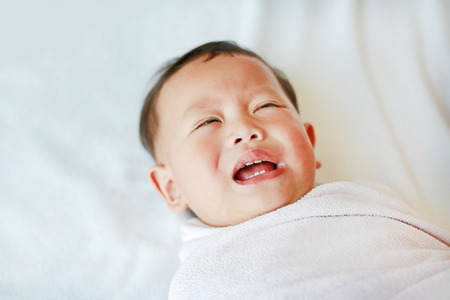 Portrait of infant baby boy crying and screaming lying on bed.