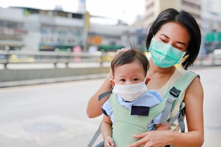 Asiatische Mutter, die ihr Säuglingsbaby auf dem Hüftsitz im Freien trägt und eine Schutzmaske gegen PM 2,5-Luftverschmutzung in der Stadt Bangkok trägt. Thailand.
