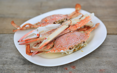 Steamed horse crab or blue crab in white plate on wood table. Seafood in Thailand. Close up.