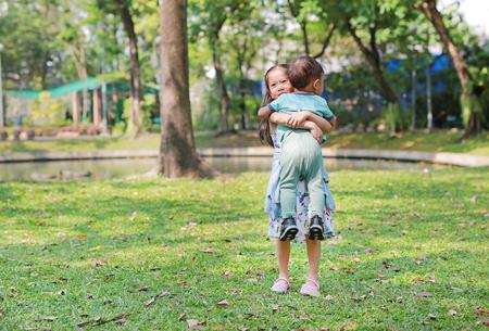 Sorella asiatica che porta il suo fratellino in giardino all'aperto.