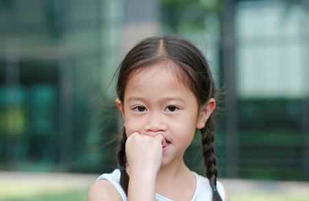 Asian little girl sucking her fingers outdoor.