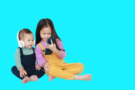 Adorable Asian older sister and little brother sharing to enjoys listening music with headphones by smartphone isolated over cyan background with copt space. Sharing concept.