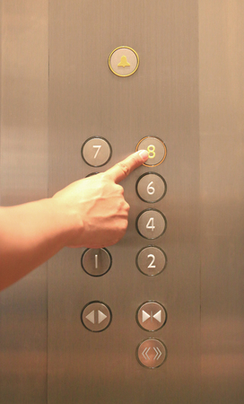 Forefinger pressing the eighth floor button in the elevator