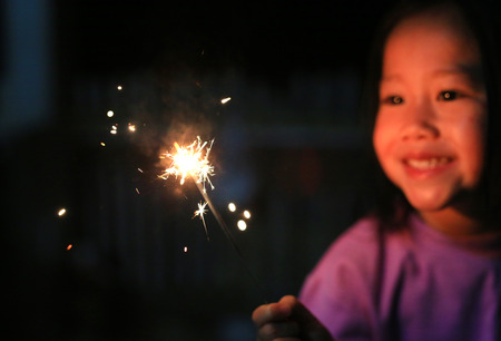Little Asian child girl enjoy playing firecrackers. Фото со стока