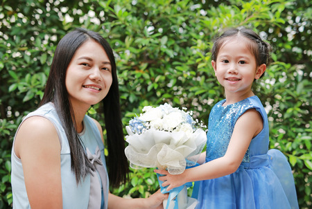 Asian child girl giving bouquet of flowers for her mother in the garden.