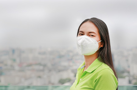 Young Asian woman wearing a protection mask against PM 2.5 air pollution in Bangkok city. Thailand. Reduce air pollution concept.