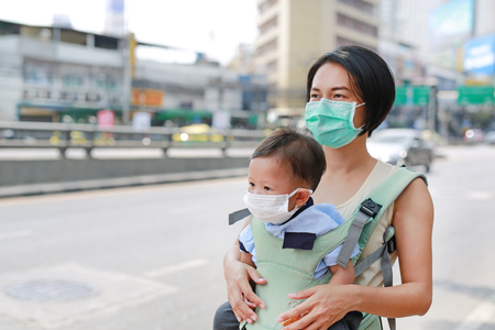 Asian mom carrying her baby by hipseat walking with wearing a protection mask against air pollution in Bangkok city. Thailand.