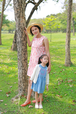 Happy Asian mom and daughter relaxing in the summer park.