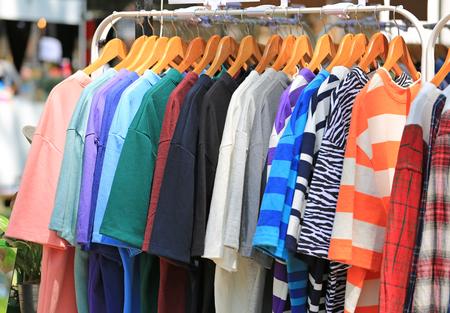 Vestiti casuali appesi allo stendibiancheria in vendita. Archivio Fotografico
