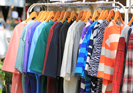 Vrijetijdskleding hangt te koop aan een kledingrek. Stockfoto