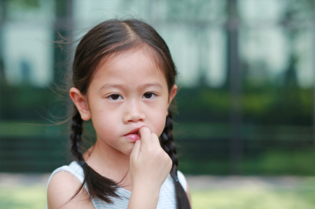 Child girl intend sucking her fingers. The gestures of children who lack confidence.