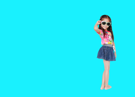 Adorable little Asian child girl wearing a floral pattern summer dress and sunglasses isolated on cyan background with copy space. Summer fashion kid concept. Full length in studio shot.