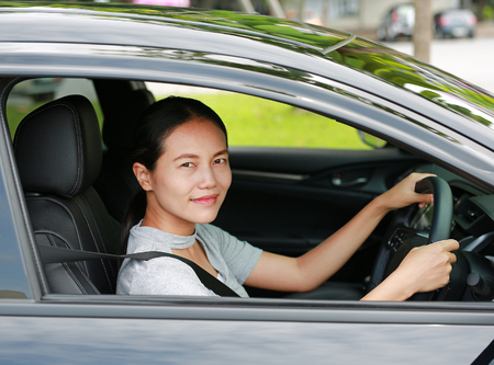 Happy young asian woman in a car while driving. Stock Photo