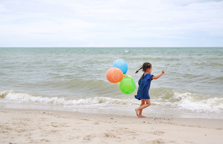 """Cute little child girl playing balloons with text """"Happy Birthday"""" on the beach Stock Photo"""