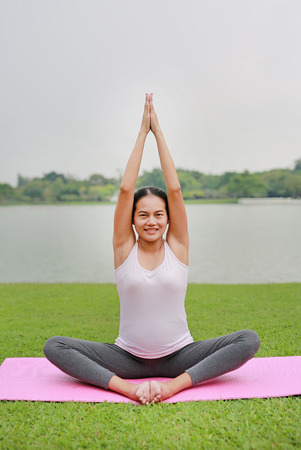 Beautiful Asian pregnant mother doing yoga in the public park near a lake. 免版税图像