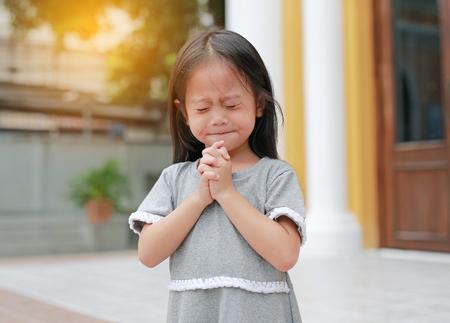 Petite position de fille asiatique priant dans le jardin le matin. Petite main de fille d'enfant priant, mains jointes dans le concept de prière pour la foi, la spiritualité et la religion.