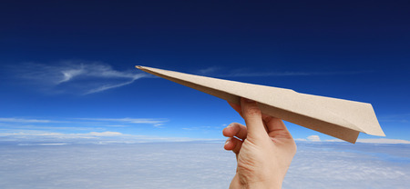 Brown aircraft rocket paper in hand on puffy cloud sky background.