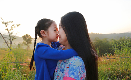 Close up Asian mother and daughters kissing in the meadow field at morning sunrise.