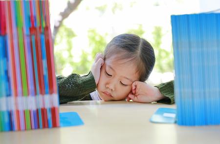 Tired little Asian girl lying on bookshelf at library. Education concept.