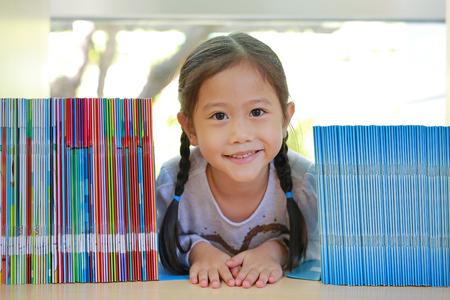 Happy little Asian child girl lying on bookshelf at library. Children creativity and imagination concept. Reklamní fotografie