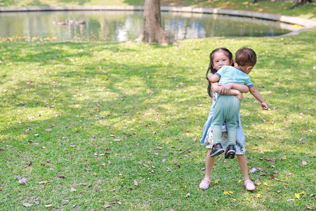 Asian sister carrying her little brother in the garden outdoor. Stock Photo