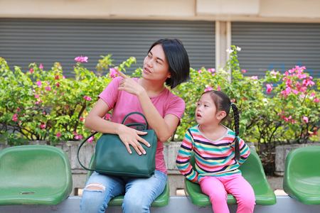 Asian mom and her daughter sitting on public transport bus. Mom pointing something to child girl looking. Stockfoto