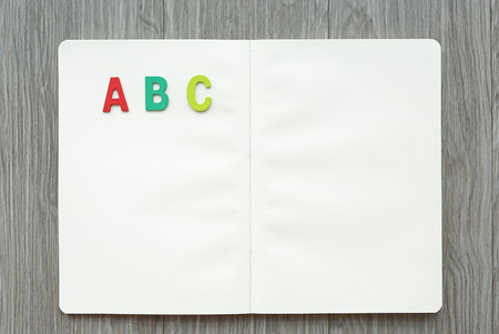 Opened blank book with letters ABC on wood table. Education concept. Stock Photo