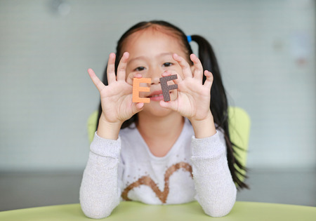 Adorable little Asian child girl holding alphabet EF (Executive Functions) text on her face. Education concept. Stock Photo