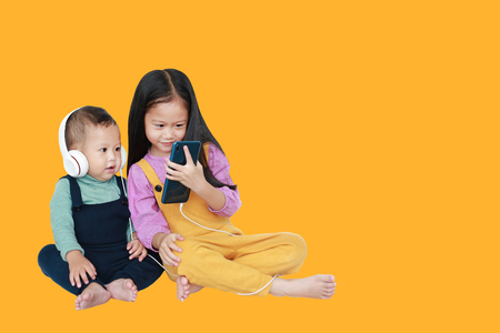 Adorable Asian older sister and little brother sharing to enjoys listening music with headphones by smartphone isolated over yellow background with copy space. Sharing concept.