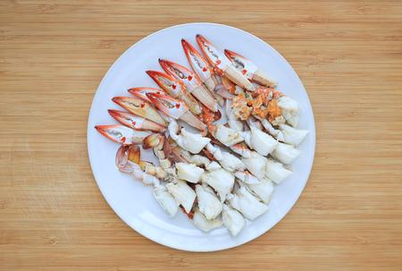 Gedämpftes Krabbenfleisch in weißer Kreisplatte auf Holzbretthintergrund. Fertig für den Verzehr. Ansicht von oben. Standard-Bild