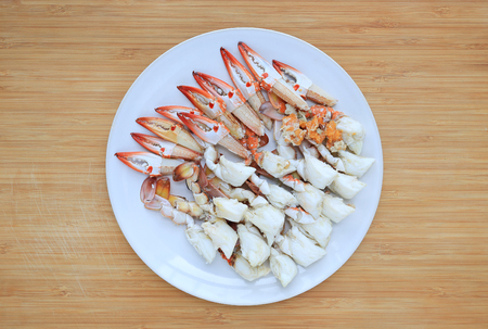 Steamed crab meat in white circle plate on wooden board background. Ready to eat. Top view. Stock Photo