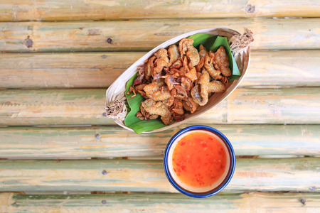 Crispy Fried Chicken Skins served on dry leaves bowl with sweet spicy sauce. Stock Photo