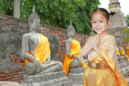 Portrait of asian child girl in traditional thai dress praying against old buddha statue at ayutthaya in thailand.