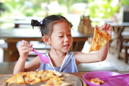 Happy little Asian child eating pizza on the table.