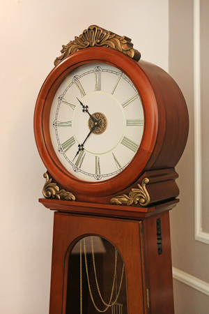 Antique style standing pendulum clock in the house.