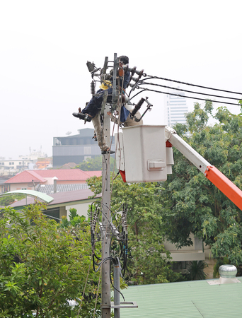 Electricians resting while working on electricity pole. Imagens