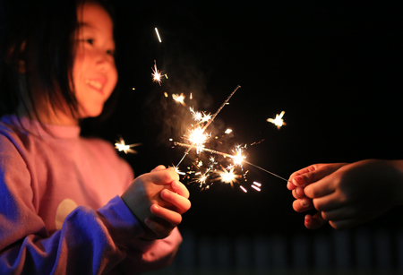 Children are playing with fire sparklers on the festival. Standard-Bild