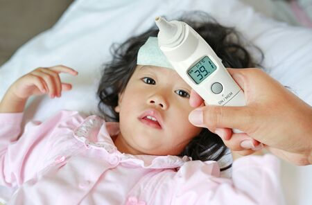 Closeup mother hand takes temperature for her daughter with high pressure of ear thermometer on bed at home. 免版税图像