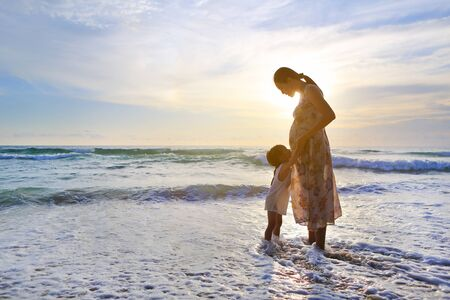 Silhouette daughter embracing pregnant mother relaxing on the beach at sunset. Stock Photo