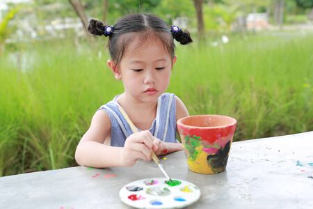 Child painting, Portrait little girl having fun to paint on earthenware dish. Фото со стока