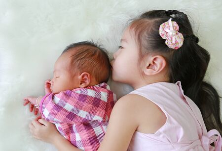 Adorable Asian sister kissing newborn baby lying on white fur background. Фото со стока