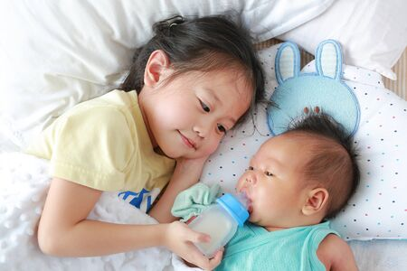 Happy sister feeding milk from bottle for her brother and lying on the bed.
