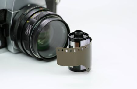 Simple old analog camera with film on white background