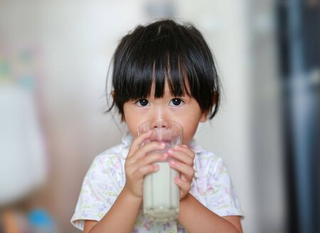 Cute Little girl in pajamas drinking milk from glass indoor at the morning.