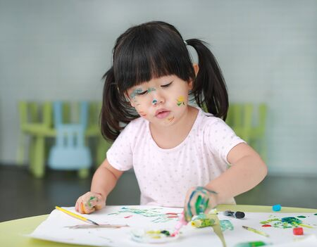 Child girl painting with paintbrush and water colors.