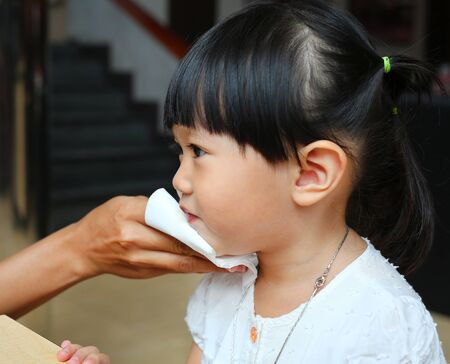 Mother wipes baby's mouth with tissue paper.